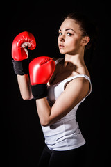 Beautiful young woman in a red boxing gloves