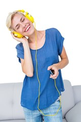 Happy blonde woman listening music with her mobile phone
