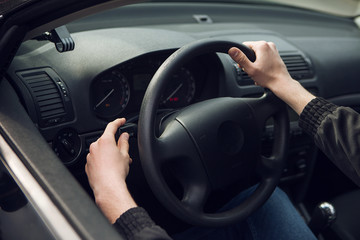 Close-up of  male hand on steering wheel in car