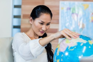 Pretty businesswoman looking at globe