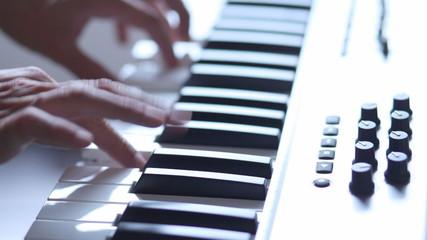 Keyboard player practicing - closeup, backlit