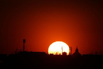 sole al tramonto a roma con antenne