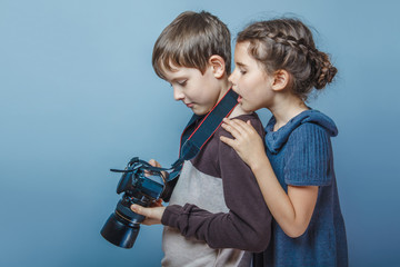 Teenage boy with a girl watching pictures on the camera on a  gr