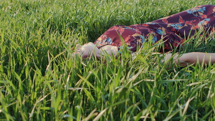 Pretty girl relaxing outdoor in green grass