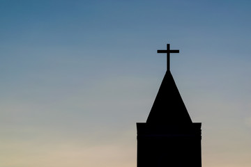 Silhouette shot of single cross on church over blue sky