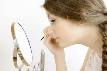 Frau schminkt sich vor Schminkspiegel