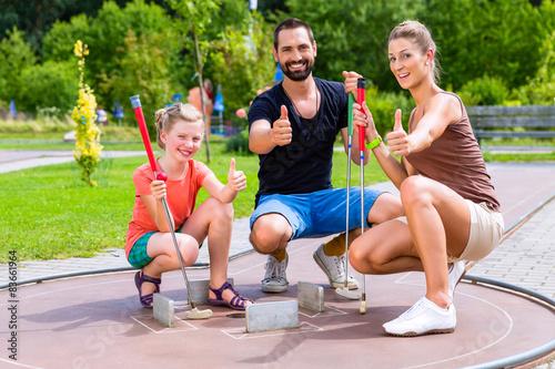 Fototapeta Familie spielt draußen zusammen Minigolf