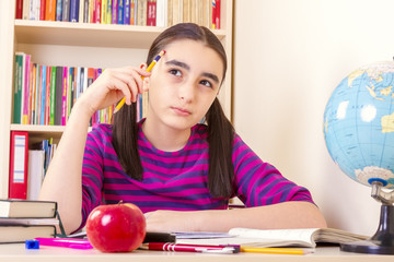 Little schoolgirl holding a pencil and thinking
