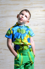Little boy in colorful clothes standing thinking