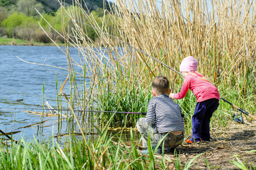 Two Siblings Holding Fishing Rods at the Riverside