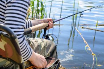 Young boy sitting fishing at a lake
