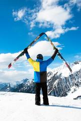 Skifahrer hält die Ski in den Himmel