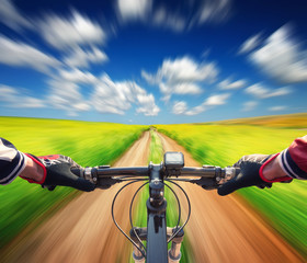Ride on bicycle on summer field. Sport and active life concept