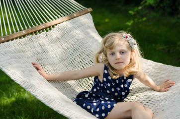 blond girl in white hammock