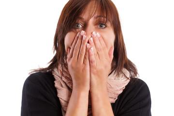 Frau ist entsetzt und hält sich den Mund zu