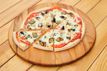 Sliced pizza with ham, aubergine, black olives and corn