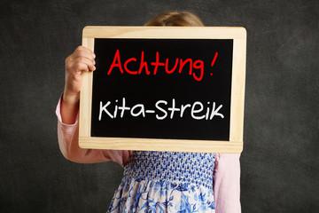 Kind hält Tafel Achtung Kita-Streik