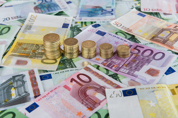 Euro banknotes and coins in example of falling euro prognoses.