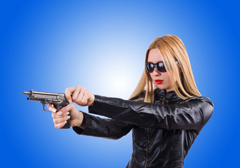 Woman in leather suit with handgun