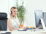 Smiling young woman working in a call center