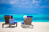 Lounge chairs with bag and hat on tropical white beach