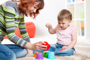 cute mother and her daughter playing together indoor