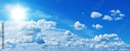 Foto Murales White heap clouds and bright sun in the blue sky.