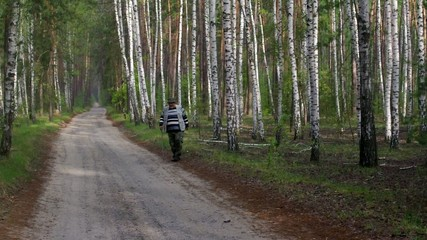 Senior man has morning walking practice in a birch forest