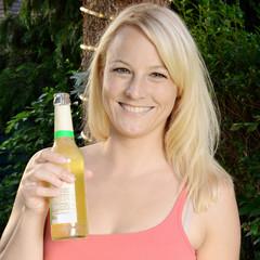 Frau trinkt Limo auf Gartenparty
