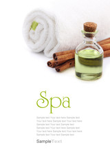 Spa concept. Green oil, cinnamon and towel, isolated on white.