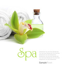 Spa concept. Green orchid, oil and white towels.