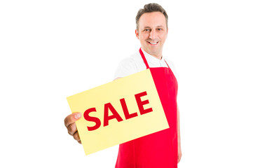 Supermarket employee holding sale sign