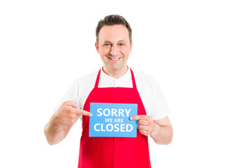 Supermarket employee holding closed sign
