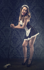 Vintage pin up maid's uniform, holding a broom