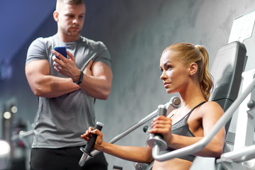 man and woman flexing muscles on gym machine