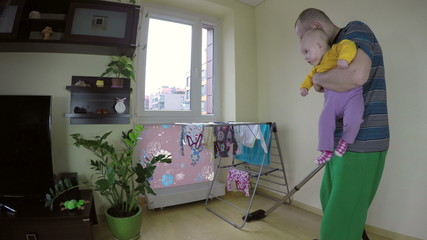 father clean room with hoover holding little baby girl on arm.