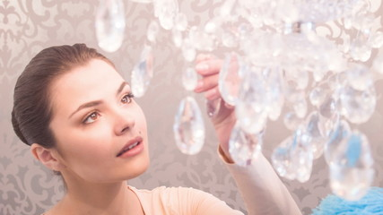 Young woman dusting chandelier
