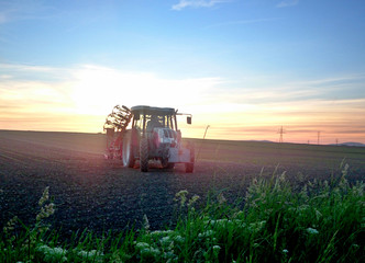 Tractor in field at sunset