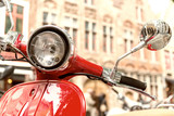 Old fashioned red motorbike parked in city center