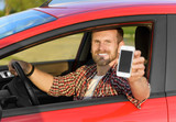 Fototapety Man in car driving showing smart phone.