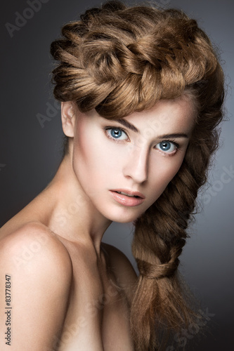 Fototapeta Beautiful girl with light make-up, perfect skin and hairstyle as a braid. Picture taken in the studio on a gray background