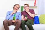 Two guys yawning on the couch during a boring party