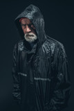 Serious Bearded Senior Man in Black Raincoat
