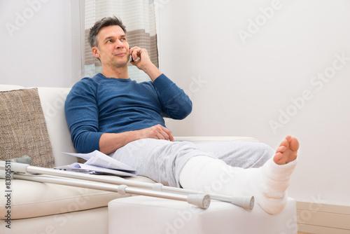 Niepełnosprawny mężczyzna rozmawia przez telefon komórkowy