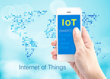 Hand holding smartphone with Internet of things (IoT) word at do poster