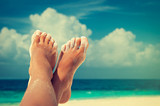 Tanned well-groomed feet amid tropical turquoise sea