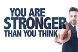 Business man pointing the text: You Are Stronger Than You Think poster