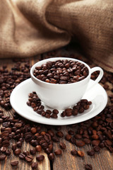 Cup full of coffee beans on brown wooden background