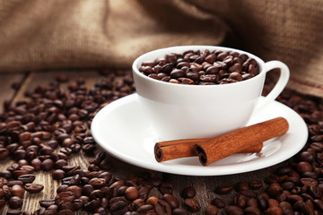 Cup full of coffee beans with cinnamon on wooden background