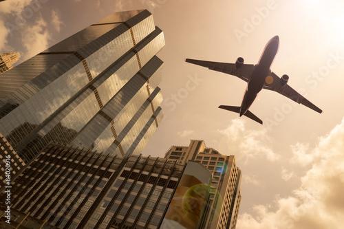 Fototapeta Airplane in golden sky with modern buildings